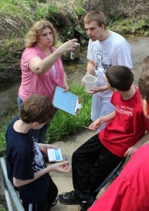 Michelle Hamilton of Des Moines takes a temperature reading during the Polk County Water Quality Snapshot with sons Jacob (top right), Jordan (bottom left) and Justin (bottom right).