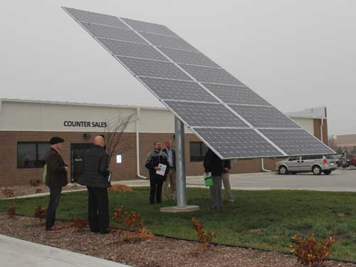 Legislators and solar energy experts inspect a solar array at Van Meter Inc. in Urbandale.
