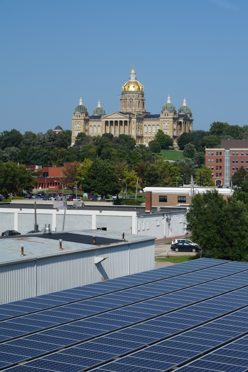 The Iowa State Capitol overlooks solar panels on PV panels on the roof of the Market One and its adjacent parking lot canopy. The Market One Building  was designed by Modus Engineering, which has developed Iowa's first commercial office building with a net-zero design.